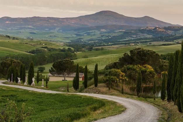 Tipico paesaggio toscano dopo il tramonto con la strada tortuosa cipressi colline e prati italia