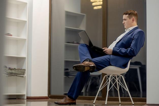 Tipica giornata lavorativa. primo piano di un giovane imprenditore fiducioso seduto nel suo ufficio e guardando lo schermo del laptop.
