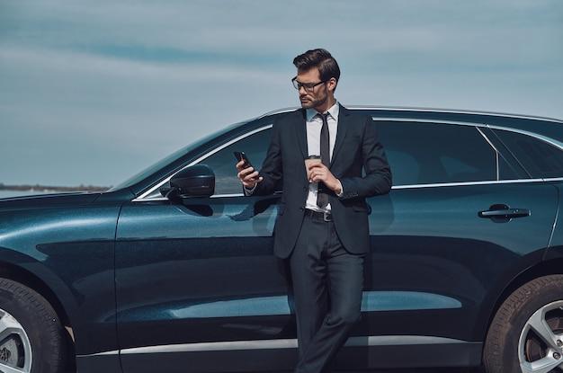 Digitando un messaggio aziendale. bel giovane uomo d'affari che usa lo smartphone e beve caffè mentre si trova vicino alla sua auto all'aperto