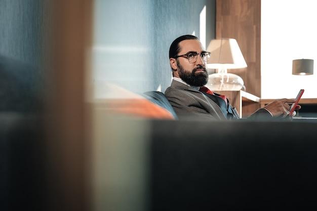 Digitazione del messaggio. uomo barbuto dagli occhi scuri che scrive un messaggio per il suo amico durante un viaggio d'affari