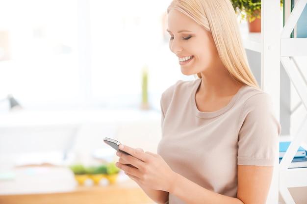 Digitando il messaggio al collega. bella giovane donna appoggiata allo scaffale in ufficio e sorridente mentre tiene il cellulare