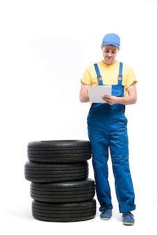 Addetto al servizio pneumatici in uniforme con notebook contro mucchio di pneumatici, bianco, riparatore, montaggio ruote