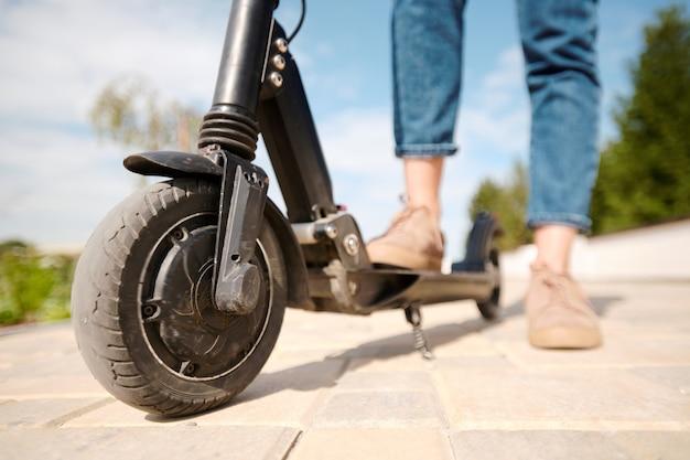 Pneumatico della ruota di scooter elettrico di giovane donna contemporanea in piedi sulla strada e facendo una breve pausa sulla strada di casa dopo il lavoro