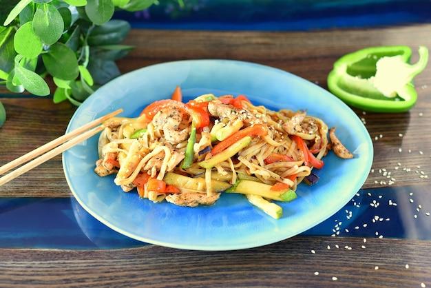 Udon con pollo e verdure in salsa di soia su un tavolo