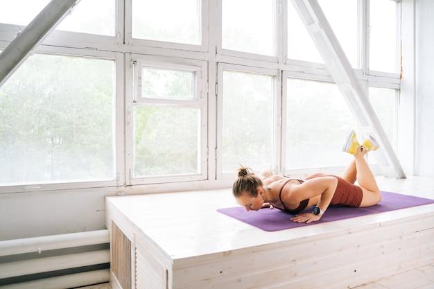 Ufa, russia - 15 maggio 2020. giovane donna muscolosa con un corpo atletico perfetto che indossa abbigliamento sportivo facendo esercizi di flessioni sul davanzale della finestra durante l'allenamento. concetto di stile di vita sano