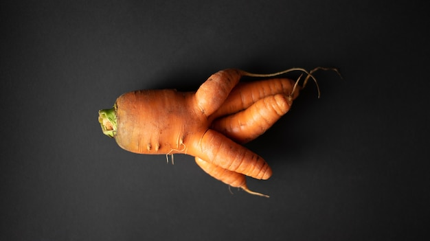 Brutta carota su uno sfondo nero scuro vista dall'alto