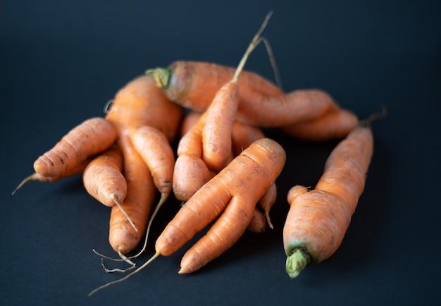 Brutte carote su uno sfondo nero scuro vista dall'alto