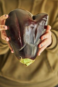 Brutta melanzana a forma di cuore che tiene con due mani. divertente, anormale vegetale o concetto di spreco alimentare.