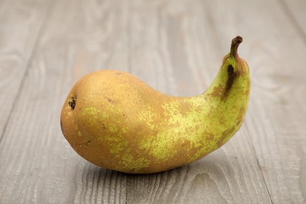 Brutto frutto. una brutta forma di pera su uno sfondo grigio con una trama di legno.