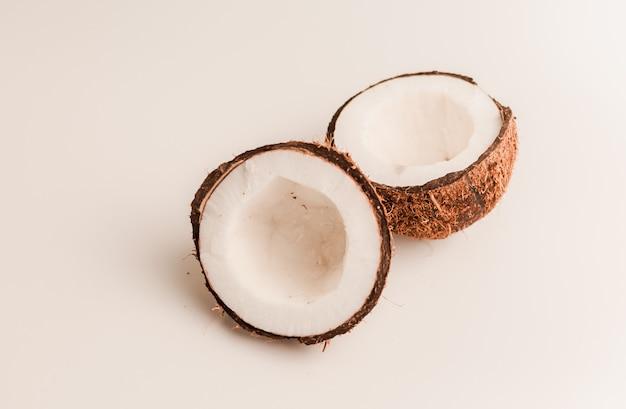 Noce di cocco organica brutta su un bianco, isolato. un dado spezzato in un guscio interno bianco di una noce di cocco