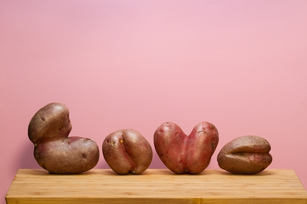 Brutte patate sul tagliere. composizione divertente sotto forma della parola amore.