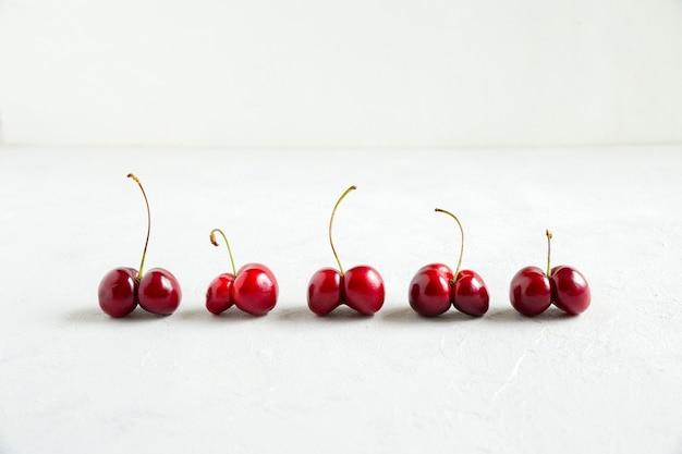 Brutte ciliege rosse su fondo bianco. fine orizzontale della composizione di orientamento su.