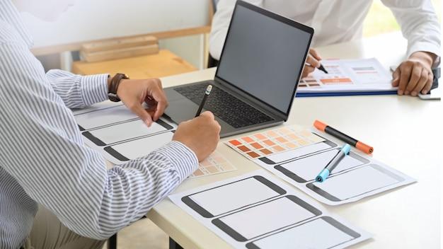 Progettista di ui ux che schizza l'applicazione di progettazione del layout sul cellulare in studio.