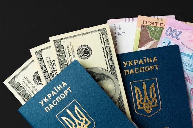 Passaporto ucraino del cittadino con i dollari americani e le banconote ucraine di grivna dentro. andare all'estero, concetto di tasso di cambio