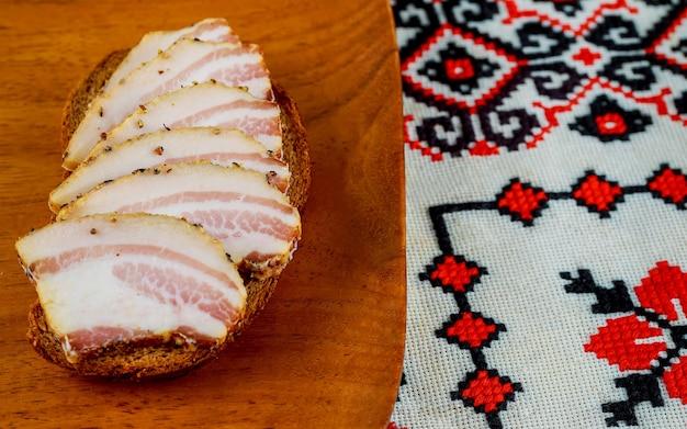 Cibo ucraino fette appetitose di salo giacciono su un tavolo da cucina scuro