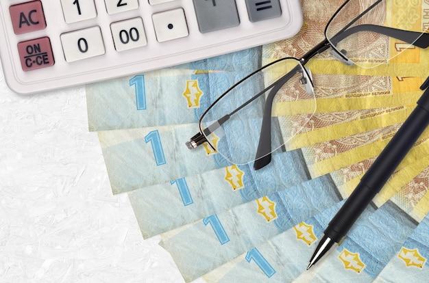 La grivna ucraina fattura il ventilatore e il calcolatore con gli occhiali e la penna