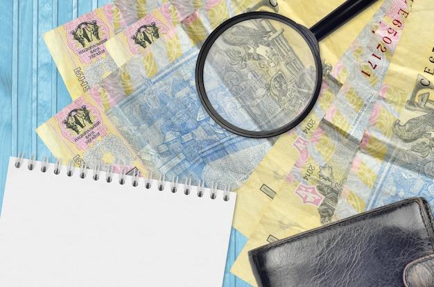 Banconote in grivna ucraina e lente di ingrandimento con borsa nera e blocco note