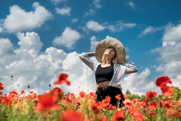Signora ucraina che cammina lungo un campo di papaveri, il concetto di sensualità, stile di vita. relax