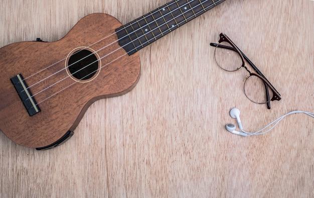Ukulele con gli occhiali e la cuffia su fondo di legno.