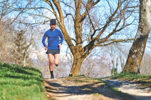Atleta uomo ultra maratona durante un allenamento in collina