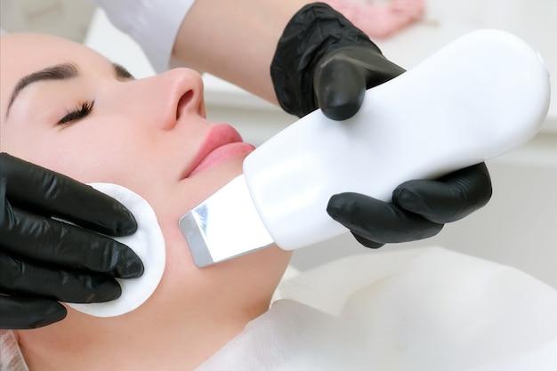 Pulizia ad ultrasuoni del viso di una giovane donna in un ufficio di cosmetologia.