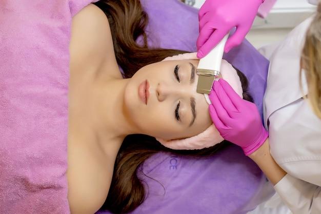 Raschiatura ad ultrasuoni. giovane donna che riceve la pulizia del peeling facciale con cavitazione ad ultrasuoni. cosmetologia pulizia del trattamento per la cura della pelle del viso. mani dell'estetista al lavoro, pulizia della pelle con getto d'acqua.
