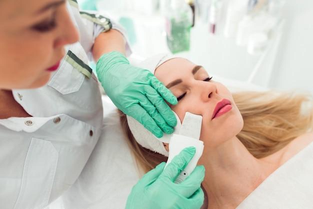 Scrubber per cosmetologia ad ultrasuoni procedura di cavitazione del viso la clinica di bellezza del cliente della giovane donna ottiene pro