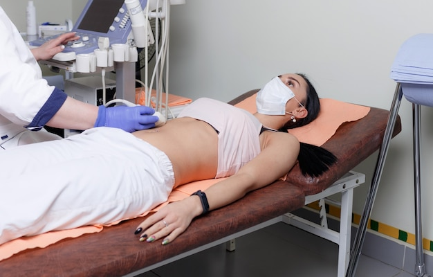 Diagnosi ecografica dello stomaco sulla cavità addominale di una donna nella clinica, vista ravvicinata. il medico esegue un sensore a ultrasuoni sulla pancia della ragazza del paziente e guarda l'immagine sul