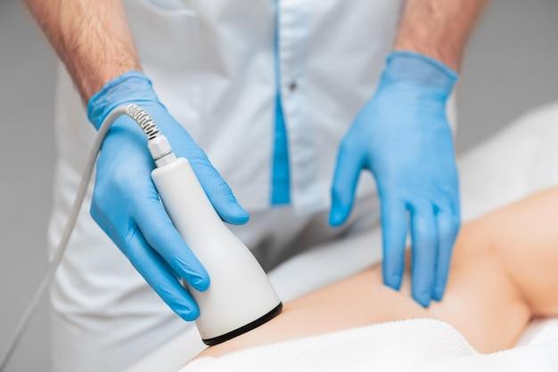 Primo piano di massaggio ad ultrasuoni sulla coscia della donna. cosmetologia hardware moderna.
