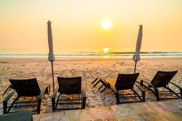 Spiaggia della sedia dell'ombrellone con la palma e la spiaggia del mare all'alba - concetto di vacanza e di vacanza