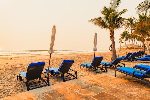 Ombrellone da spiaggia con palme e spiaggia del mare all'alba