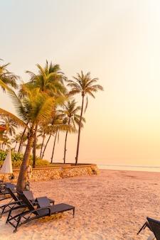 Ombrellone e sedia in spiaggia con palme all'alba