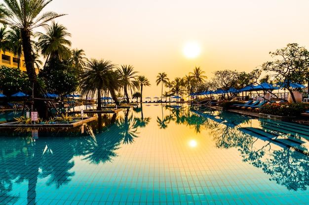 Ombrellone e sedia in piscina con palme all'alba