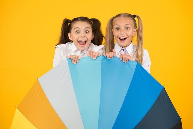 Sorpresa dell'ombrello. ragazze sorprese che si nascondono dietro l'ombrello su sfondo giallo. bambini piccoli che guardano con sorpresa. sorpresa che apre gli occhi. ritorno a scuola sorpresa.