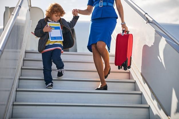 Minore non accompagnato che scende dalle scale di imbarco con hostess