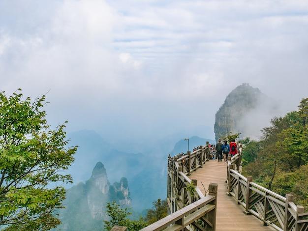 Turisti sconosciuti che camminano sul ponte di legno che attraversa la montagna