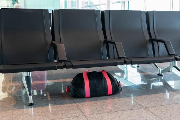 Borsa bagagli incustodita lasciata sotto la sedia in aeroporto o in autobus o in stazione. minaccia alla sicurezza pubblica e concetto di terrorismo
