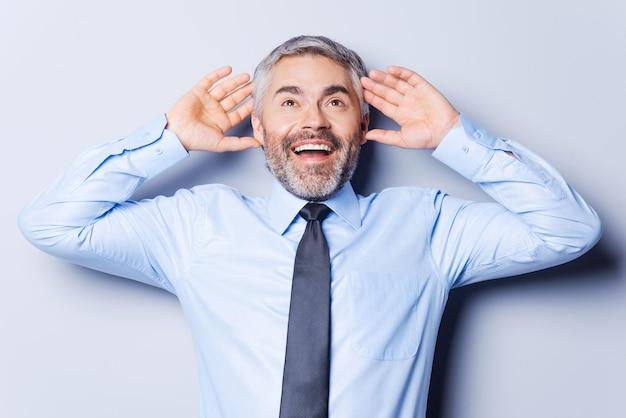 Incredibile! felice uomo maturo in camicia e cravatta che tocca la testa con le mani e sorride mentre sta in piedi su uno sfondo grigio