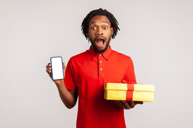 Incredibile regalo per le vacanze. uomo scioccato che tiene in mano una confezione regalo e uno smartphone con schermo vuoto.