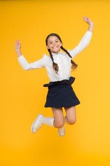 Sete sfrenata di conoscenza. ragazza sulla via della conoscenza. giornata della conoscenza. di nuovo a scuola. la studentessa allegra del bambino piena di energia salta a mezz'aria. l'alunno vuole studiare. inizio lezione. bambino attivo in movimento.