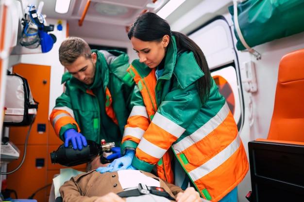 Uomo anziano incosciente e paramedici che lavorano nell'ambulanza