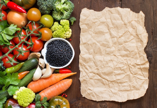 Lenticchie nere crude in una ciotola con le verdure su una tavola di legno