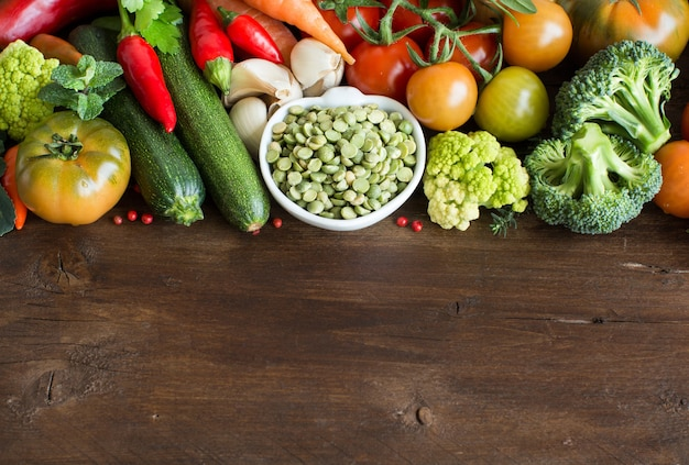 Piselli spezzati secchi crudi in una ciotola con le verdure su legno vicino con lo spazio della copia