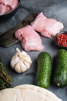 Gyros ingredienti crudi, cosce di pollo su sfondo grigio.