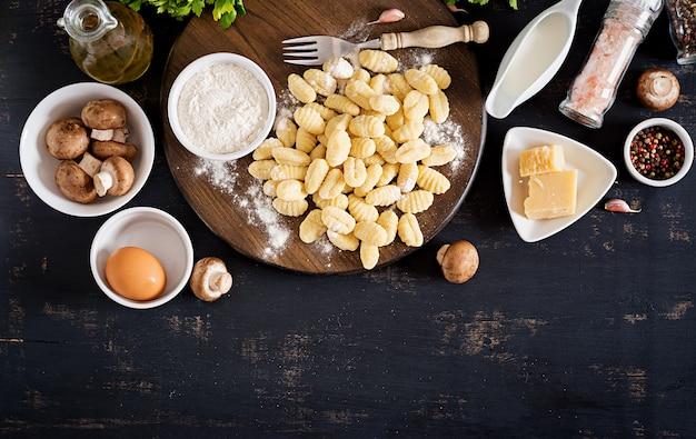 Gnocchi fatti in casa crudi con salsa di crema di funghi e prezzemolo in una ciotola su uno sfondo scuro.