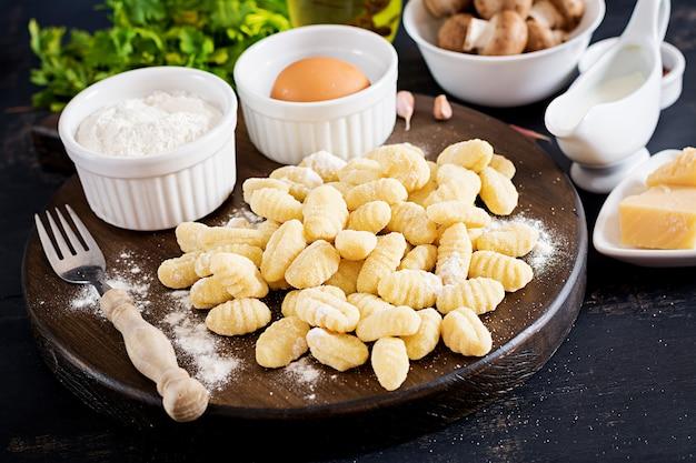 Gnocchi fatti in casa crudi con salsa di crema di funghi e prezzemolo in una ciotola su un tavolo scuro.