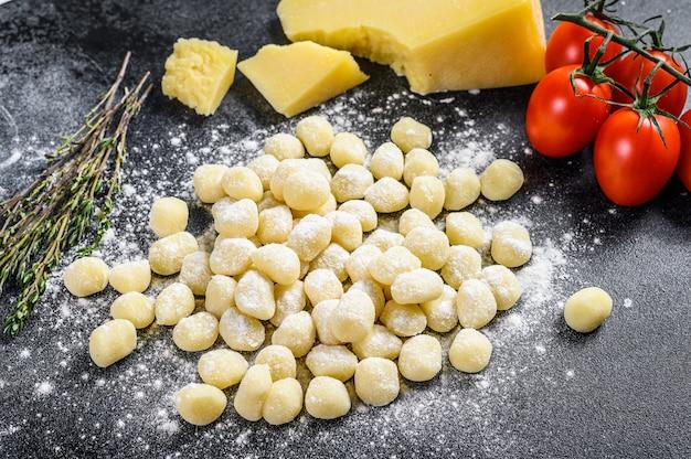 Gnocchi di patate fatti in casa crudi con ingredienti per cucinare la pasta. vista dall'alto