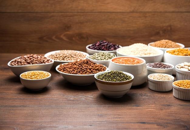 Legumi indiani crudi, cereali e semi in ciotole bianche su una superficie di legno. messa a fuoco selettiva
