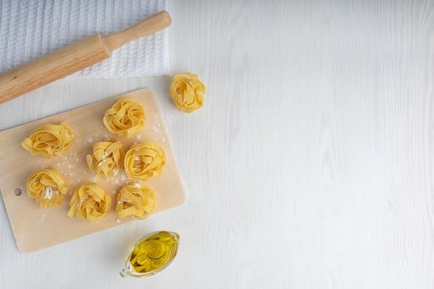 Pasta italiana cruda di fettucine sul tagliere insieme al mattarello sul tovagliolo e sulla salsiera dell'olio d'oliva. vista dall'alto