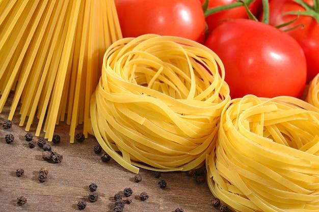 Pasta italiana cruda, ramo di pomodori maturi e pepe nero su fondo di legno